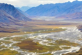 Photo of high artic mountain valley, with braided river winding its way though wide floodplain