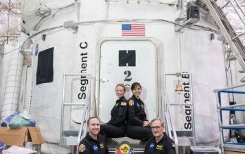 NASA crewmembers, in flight uniform, seated in front of NASA-white space capsule housed in aircraft hangar