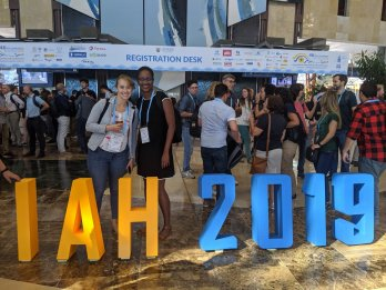 "Candid photo of Sarah McKnight (left) and Marsha Allen (right) in front of crowd at a conference center, standing behind knee-high orange and blue block letters saying ""IAH 2019"""