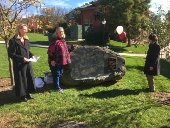 Dr. Julie Brigham-Grette, Johanna Andersen-Pratt, and Dean Serio stand in front of a boulder of pillow basalt from the Ordovician Hawley Formation in the Morrill courtyard