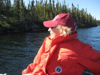 Photo of the late Dr. Sheila Seaman, illuminated by sunlight and sitting reclined in a boat in a lake in the middle of a Canadian boreal forest, facing towards viewer but looking left, wearing sunglasses and field jacket / PFD. She is smiling.