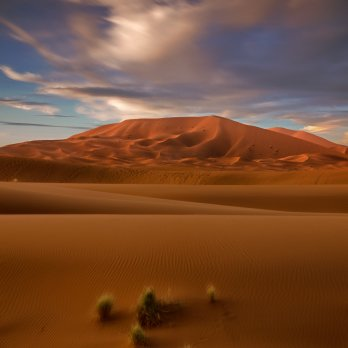 Brown hill in a sandy desert landscape under partly cloudy blue sky near the end of day.