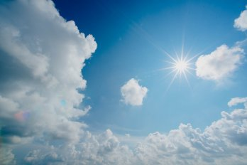 Sun and clouds in clear blue sky
