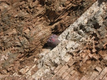 Rocks near Gubbio, Italy, change in color and texture at the line indicating the Cretaceous-Paleogene extinction event that wiped out the dinosaurs 66 million years ago. A baseball hat shows scale. Photo by Dr.'s Robert DeConto and Mark Leckie, UMass Geosciences, CC BY-ND
