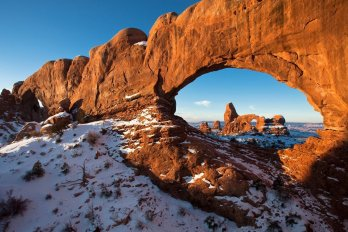 Orange sandstone rock arch in snowy desert landscape with clear blue sky (Turret Arch)