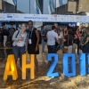 """Candid photo of Sarah McKnight (left) and Marsha Allen (right) in front of crowd at a conference center, standing behind knee-high orange and blue block letters saying """"IAH 2019"""""""