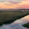 A water channel through a salt marsh during a dusky pink sunset.